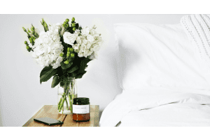 White bedding with side table that has a vase of flowers, a candle and a mobile phone