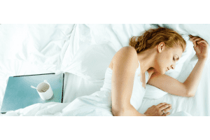 Woman sleeping on bed with laptop and coffee mug next to her